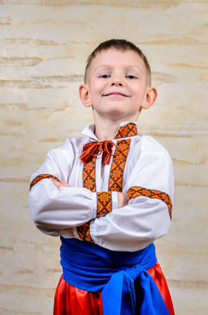 Happy child posing with folded arms proud to wear the Ukrainian traditional folk costume, with symmetrical embroidered motifs and blue belt on white shirt, portrait Standard-Bild