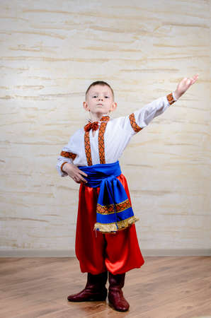 Little boy in colorful costume doing folk dancing posing with his arm raised for the start or finish of the dance Standard-Bild