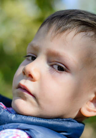 expressionless: Close Up Portrait of Young Boy Looking Serious Sideways at Camera in Outdoors Environment