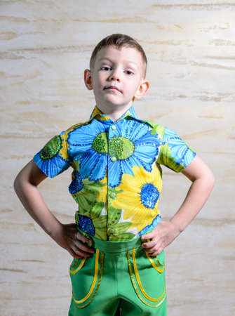 disapproving: Young Boy Wearing Colorful Floral Print Collar Shirt Standing with Hands on Hips and Looking Serious in Studio with Patterned Background
