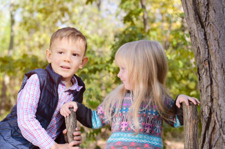 Portrait of Boy and Girl Outdoors in Wooded Forest Area, Brother and Sister Spending Time Together Outdoors photo