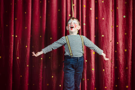 Young Boy Dressed as Clown Performing on Stage with Open Arms and Open Mouth as if Singing or Acting