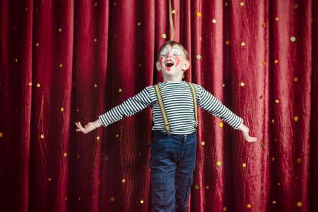 payaso: Muchacho joven vestido como payaso actuando en el escenario con los brazos abiertos y la boca abierta como si canto o interino
