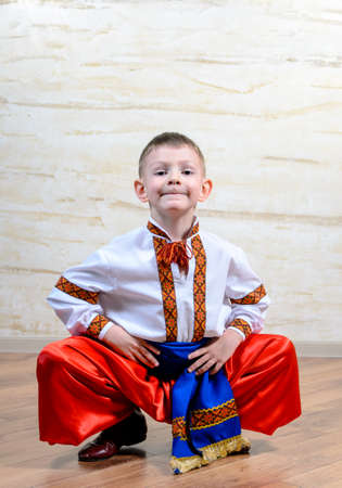 expressionless: Ukrainian talented child performing a traditional dance move with a leap in mid air while wearing folk costume during a cultural artistic representation Stock Photo