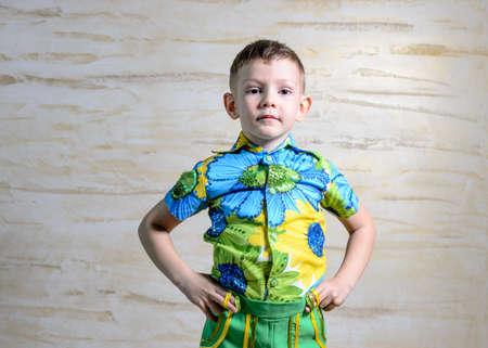 disapproving: Giovane ragazzo che indossa coloratissimi shirt con stampa floreale collare in piedi con le mani sulle anche e guardando gravi in ??studio con sfondo modellata Archivio Fotografico