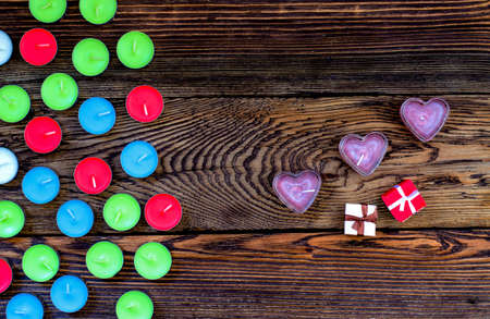 unlit: High Angle View of Colorful Unlit Tealight Candles Arranged to One Side with three Heart Shaped Purple Candles and two gifts on the Other with Wooden Background Stock Photo