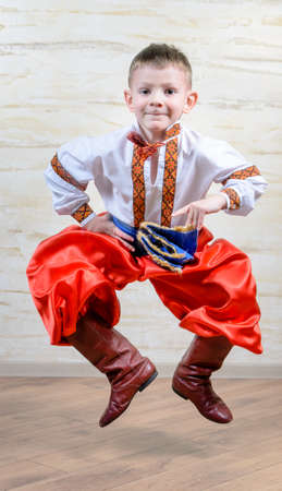 discriminating: Ukrainian talented child performing a traditional dance move with a leap in mid air while wearing folk costume during a cultural artistic representation Stock Photo