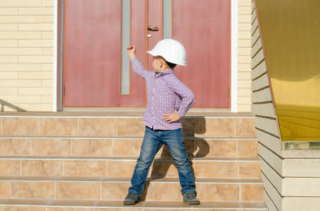 make believe: Young Boy Dressed as Construction Worker Foreman Wearing White Hard Hat Standing on Steps of Building and Motioning with Hand Behind Him Stock Photo
