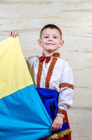 identidad cultural: Niño lindo que desgasta el traje popular con bordado tradicional decorativa mientras sostiene la bandera nacional de Ucrania, retrato con la expresión facial grave Foto de archivo