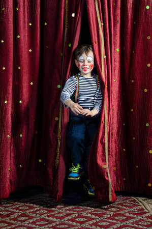 dramatically: Young Boy Dressed as Clown Jumping Dramatically Through Opening in Red Curtains in Dramatic Stage Entrance Stock Photo
