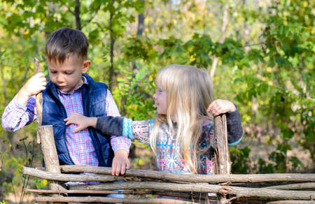 camaraderie: Two Cute Male and Female White Kids, Wearing Autumn Outfit, Playing at the Wooden Fence of the Garden.