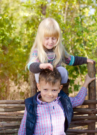 Cute Smiling Blond Girl Playing the Hair of her Brother, Who is Smiling at the Camera, While at the Garden Fence During Autumn Season. photo