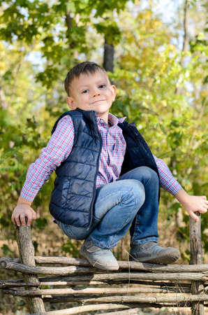 expressionless: Portrait of Young Serious Boy Wearing Plaid Shirt and Vest Leaning on Crossed Arms on Top of Rustic Wooden Fence in Forest