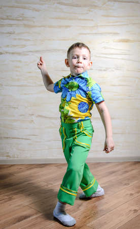 discriminating: Young Boy Wearing Green Pants and Floral Print Shirt Snapping Fingers and Performing Traditional Dance in Studio Stock Photo