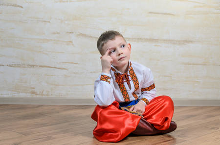 expressionless: Cute young boy sitting on a wooden floor in a colorful dance or pantomime costume scratching his head and thinking with a puzzled expression