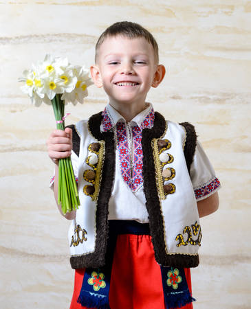 eastern european: Adorable little boy smiling and wearing traditional Eastern European folk costume, with embroidered motifs on vest and shirt, while holding a daffodil bouquet, portrait Stock Photo