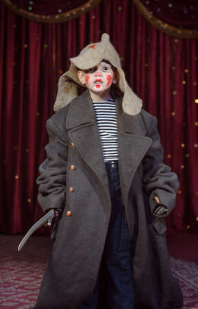 Young Boy Dressed in Over Sized Grey Coat and Floppy Hat Holding Prop Toy Sword with Face Painted in Clown Make Up, Standing on Stage Looking at Camera photo