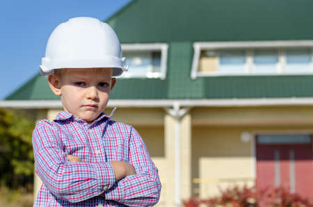 motioning: Young Boy Wearing Plaid Shirt and White Hard Hat Standing in front of House, Motioning with Hand as if Presenting Finished Home