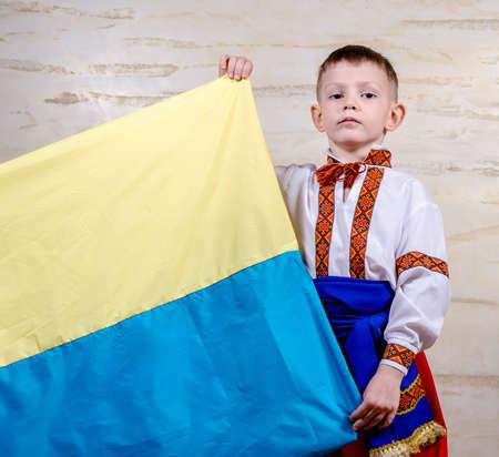 identidad cultural: Ni�o lindo que desgasta el traje popular con bordado tradicional decorativa mientras sostiene la bandera nacional de Ucrania, retrato con la expresi�n facial grave Foto de archivo