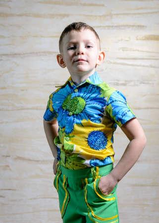 disapproving: Giovane ragazzo che porta Colorful stampa floreale Camicia piedi con le mani sulle anche in studio con sfondo modellata, Rivolto disapprovazione Camera