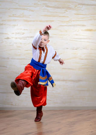 eastern european: Talented child wearing Eastern European folk costume with embroidered white shirt and belt, red pants and boots, in a mid-air leap while performing a traditional dance