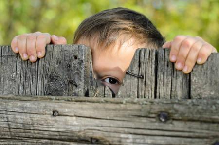 portones: Cerrar un Hombre joven ni�o que mira a escondidas sobre una cerca de madera r�stica Mientras sostiene el borde y mirando a la c�mara Foto de archivo