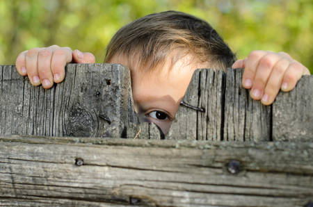 in behind: Close up Male Young Kid Peeking Over a Rustic Wooden Fence While Holding the Edge and Staring at the Camera Stock Photo