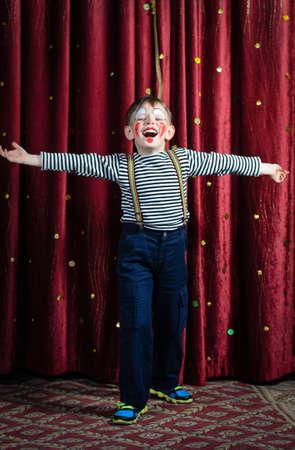 Jonge jongen kleedde zich als Clown op het podium met open armen en Open Mond alsof Zingen of Acting