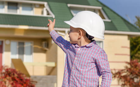 make believe: Young Boy Wearing Plaid Shirt and White Hard Hat Standing in front of House, Motioning with Hand as if Presenting Finished Home