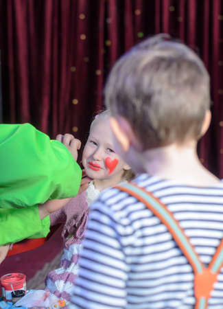 clowning: Young Boy Watching as Girl Has Face Painted by Adult - Young Blond Girl Having Make Up Applied to Face While Boy Looks On