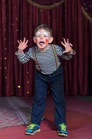 Boy Wearing Clown Make Up, Striped Shirt and Suspenders Making Face and Hand Gestures on Stage Towards Camera