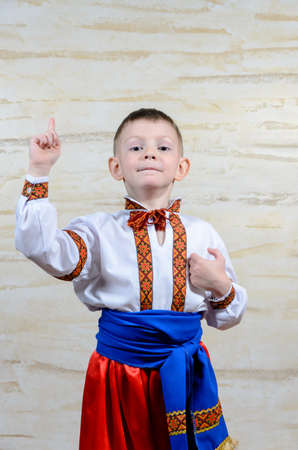 Adorable happy child pointing up while wearing an authentic Ukrainian folk costume with handmade decorative embroidered borders on white shirt and blue silky belt