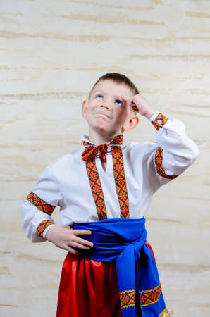 dance preteen: Adorable happy child pointing up while wearing an authentic Ukrainian folk costume with handmade decorative embroidered borders on white shirt and blue silky belt