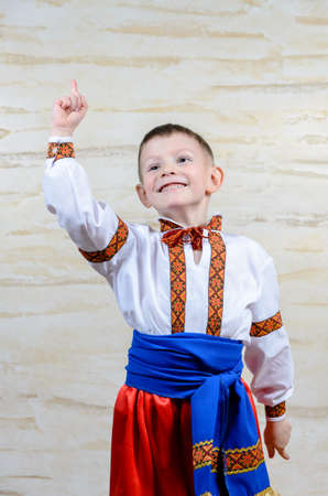 extrovert: Adorable happy child pointing up while wearing an authentic Ukrainian folk costume with handmade decorative embroidered borders on white shirt and blue silky belt