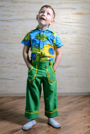 disapproving: Adorable child wearing shirt with floral pattern and green pants while standing with hands in pockets and looking up with a funny inquiring expression, full length