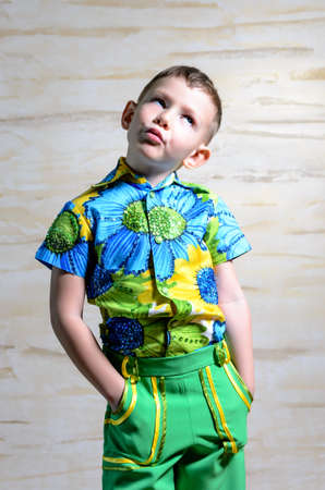disapproving: Cute little boy in colorful clothes standing thinking staring up into the air with a contemplative expression and his hands in his pockets