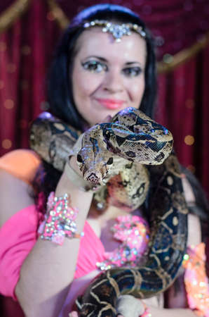symbiotic: Portrait of Dark Haired Exotic Snake Charmer Female Dancer with Large Snake Around Neck Smiling at Camera