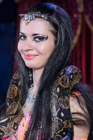 charmer: Portrait of Dark Haired Exotic Snake Charmer Female Dancer with Large Snake Around Neck Smiling at Camera