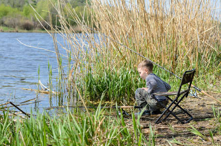 squatting down: Young boy fishing with a rod and reel on the shores of a calm lake squatting down alongside the water near a bank of reeds Stock Photo