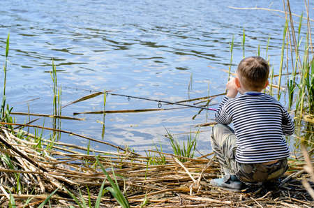 preteen boys: Rear View of a Serious Young Boy Sitting on Riverside, Holding his Fishing Rod and Waiting to Catch a Fish.