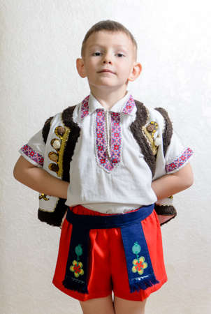 hands behind back: Ukrainian cute boy posing with hands behind back proud to wear the traditional folk costume with short pants and handmade embroideries on vest, white shirt and belt, portrait with copy space on grey Stock Photo