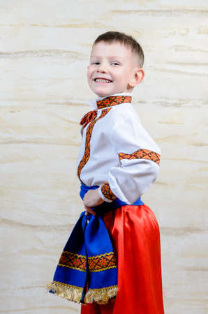 Proud young boy in a colorful dance or pantomime costume standing with his hands on his hips grinning at the camera