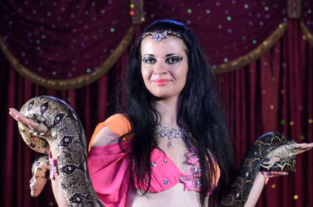 snake: Close Up of Exotic Female Snake Dancer with Dark Hair Holding Large Snake in Both Hands Standing on Stage
