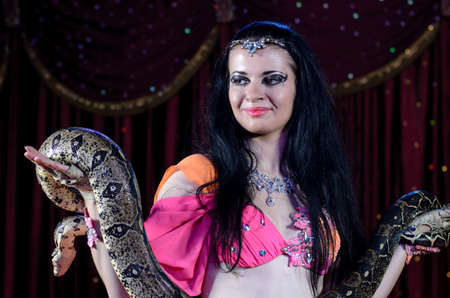 exotic dancer: Close Up of Exotic Female Snake Dancer with Dark Hair Holding Large Snake in Both Hands Standing on Stage