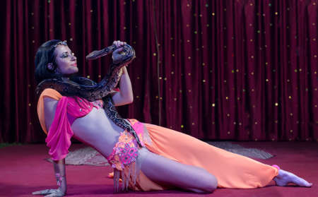 charmer: Full Length Image of Exotic Snake Charmer Dancer Reclining on Stage Floor with Large Snake Draped Around Shoulders, Fondly Looking at Snake Face to Face