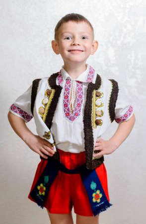ウクライナのかわいい少年ショート パンツとベスト、白シャツ、ベルト、灰色にコピー スペースを持つ肖像画手作り刺繍の伝統的な民族衣装を着る