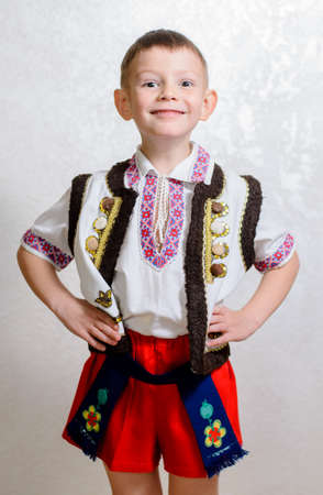 Ukrainian cute boy posing with hands behind back proud to wear the traditional folk costume with short pants and handmade embroideries on vest, white shirt and belt, portrait with copy space on grey Stok Fotoğraf