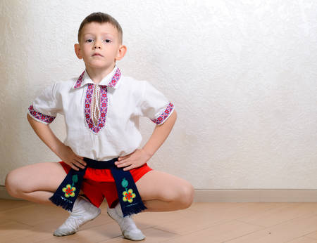 expressionless: Ukrainian serious boy, with hands on hips in squatting position, wearing traditional folk costume during an artistic performance, with copy space on grey wall
