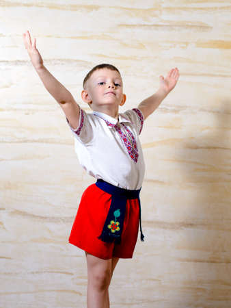 talented: Ukrainian talented boy posing with raised arms and an artistic attitude while wearing with pride a traditional folk costume with white shirt, belt and red pants