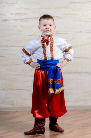 extrovert: Proud young boy in a colorful dance or pantomime costume standing with his hands on his hips grinning at the camera